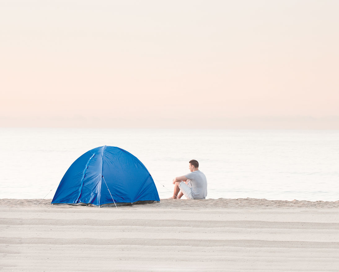 man with tent on the beach